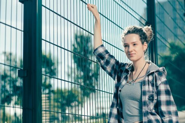 屋外にいて、金網の柵に触れながらあなたを見ている穏やかなリラックスした若い女性