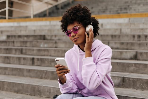 보라색 후드티를 입은 차분한 젊은 여성, 분홍색 선글라스는 헤드폰으로 음악을 듣습니다