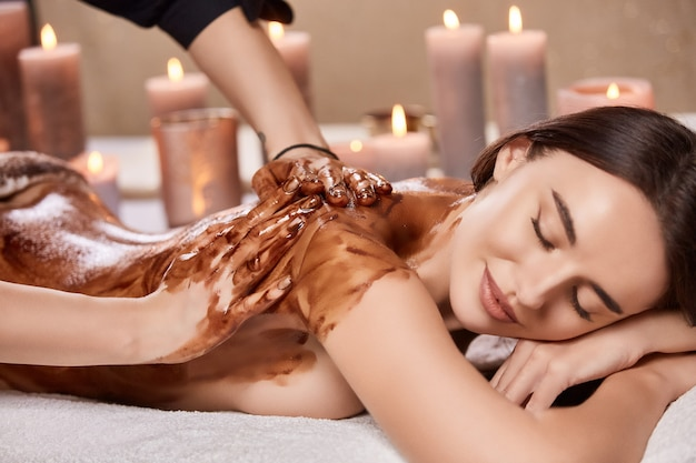 Calm and relaxing body treatment with chocolate at spa with candles