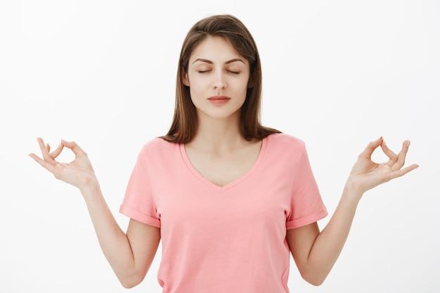 Donna castana attraente calma e sollevata che posa nello studio