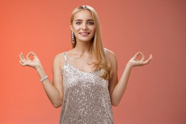 リラックスして立っている銀のスタイリッシュな豪華なドレスで落ち着いて安心した幸せな素晴らしい若いブロンドの女性