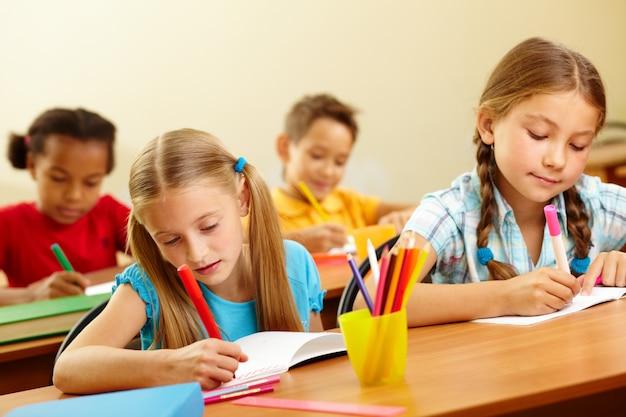 Calm schoolchildren drawing in class