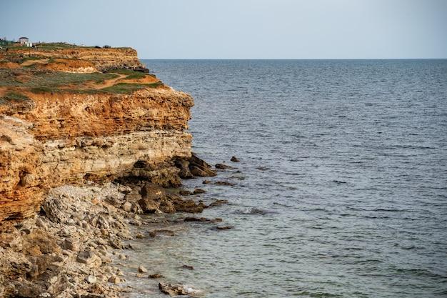 穏やかな海の波が岩の多い海岸に静かに打ち寄せ、海の景色を落ち着かせてキャンプや旅行をします