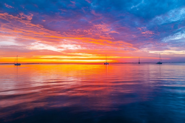 Calm sea with sunset sky and sun through the clouds over. ocean and sky background, seascape.