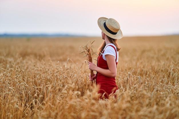 Спокойная безмятежная молодая женщина в соломенной шляпе и красном джинсовом комбинезоне стоит на золотисто-желтом сухом пшеничном поле и наслаждается прекрасным моментом свободы