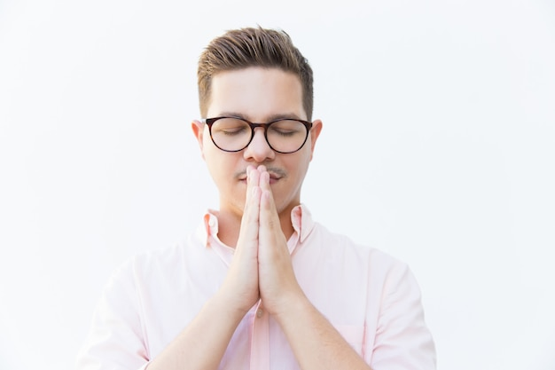 Calm serene guy in eyewear praying with closed eyes