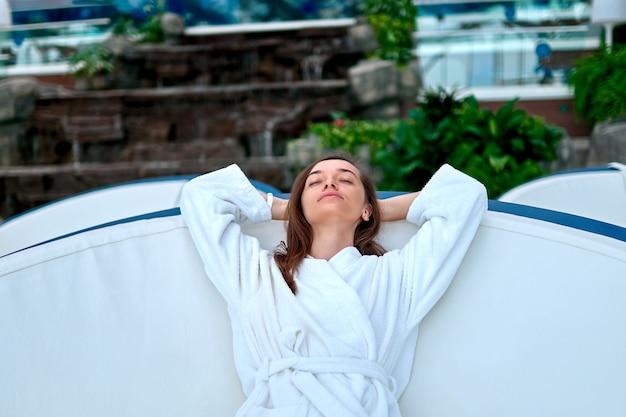 Спокойная безмятежная женщина в халате с закрытыми глазами и руками за головой расслабляется в одиночестве на оздоровительном спа-курорте. удовольствие и отдых для себя