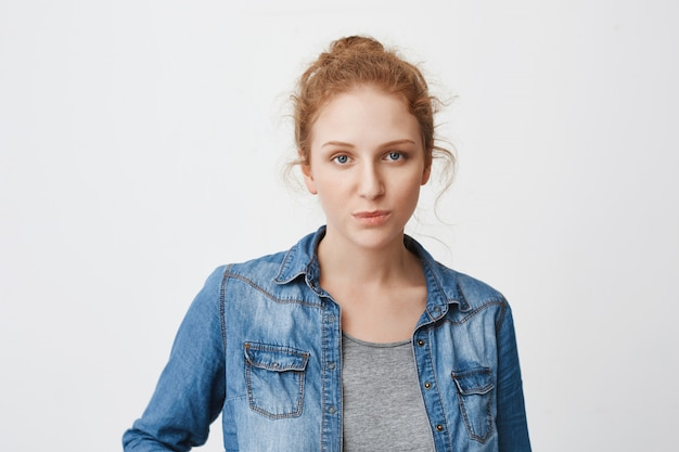 Calm serious caucasian ginger girl with hair combed in bun, expressing irritation or indifference while standing