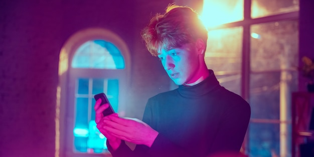 진정해, 진지해. 네온 조명이 켜진 실내에서 세련된 빨강머리 남자의 영화적 초상화. 보라색 - 파란색의 영화 효과처럼 톤. 실내에서 화려한 조명으로 스마트폰을 사용하는 백인 모델입니다. 전단.