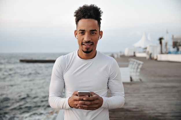 Calm serious dark-skinned man in white long-sleeved t-shirt looks into camera, holds phone and listens to music in headphones