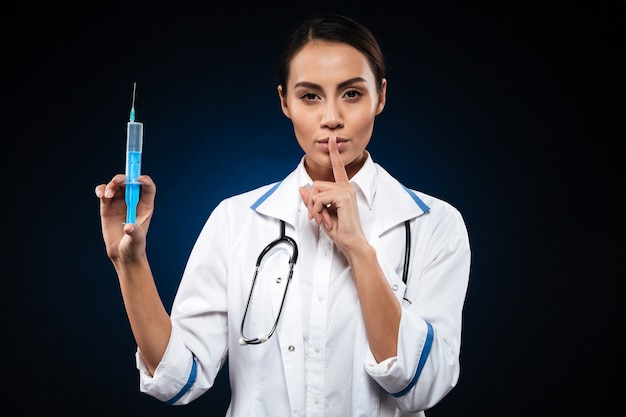 Calm serious lady holding syringe and making silence gesture isolated