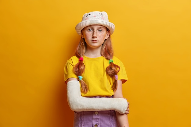 Calm serious small girl, has long ginger hair and freckled skin, wears fashionable summer outfit, poses with hand in cast, recovers after accident, isolated over yellow wall