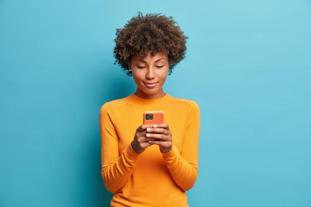 穏やかな真面目な若い女性は、電話でゲームをしたり、高速インターネットに接続されたテキストメッセージを送信したり、青い壁にカジュアルなジャンパーポーズを着た最新のテクノロジーを使用しています