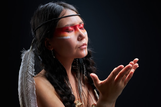 黒の壁に隔離された、インドの羽毛とカラフルな化粧をした穏やかなシャーマニズムの女性。彼女は瞑想しています。肖像画