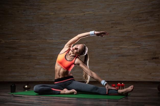 Спокойная стройная женщина в спортивной одежде сидит на коврике для йоги, положив одну руку на ногу и одну руку над головой, во время выполнения асаны со свечами на заднем плане