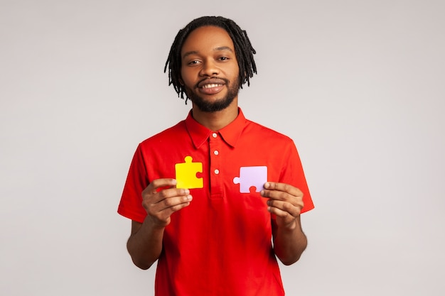 Calm smiling bearded man holding yellow and purple puzzle parts, solving problems and tasks.