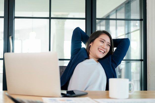 편안한 사무실 의자에서 머리 뒤로 손을 놓고 편안하게 웃고 있는 사업가, 일을 마친 후 만족스럽게 사무실에서 쉬고 있는 행복한 여성