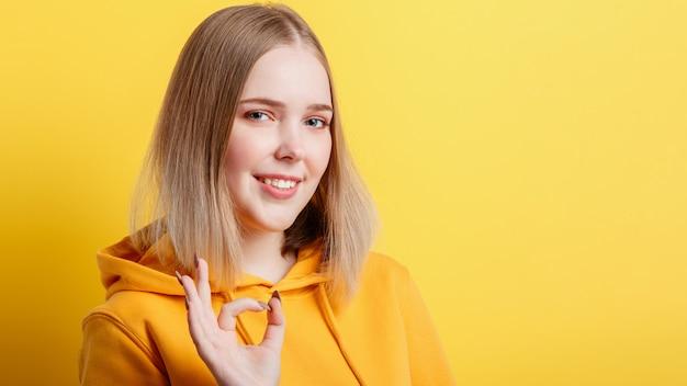 침착하게 웃고 있는 10대 금발 소녀는 노란색 배경에 격리된 긍정적인 확인 제스처 기호와 승인을 보여줍니다. 세로 젊은 여자 확인 손 제스처를 보여줍니다. 복사 공간이 있는 긴 웹 배너입니다.