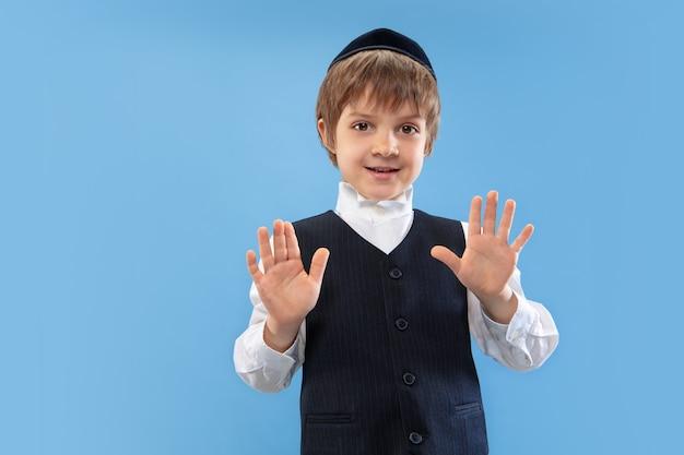 落ち着いて、やめて。青い壁に隔離された若い正統派ユダヤ人の少年の肖像画。プリム、ビジネス、お祭り、休日、子供時代、お祝いのペサッハまたは過越の祭り、ユダヤ教、宗教の概念。