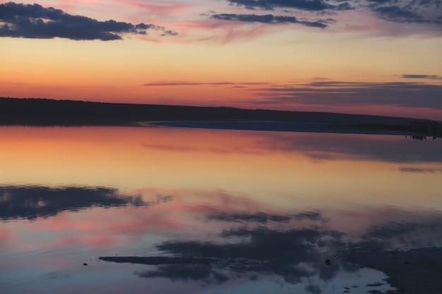 Спокойный закат с отражениями облаков в озере.