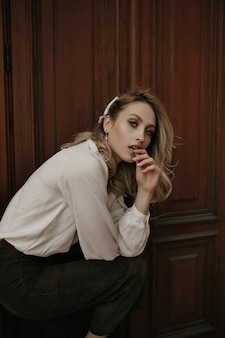 Calm thoughtful blonde young lady in dark velvet pants and white blouse looks into camera, squats near wooden door