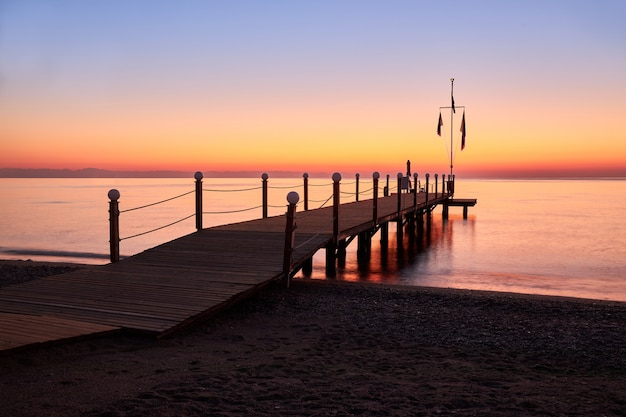 Calm warm sea and a large wooden pier with a swimming area at dawn