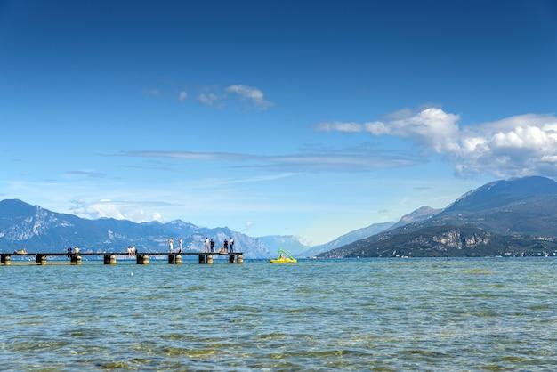 Озеро со спокойной водой в гарде, италия с деревянной дорожкой в солнечный летний день.