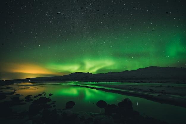 Calma dell'acqua vicino alla montagna sotto l'aurora boreale di notte