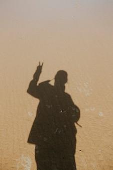 平静的水在沙滩上,一个男人的阴影