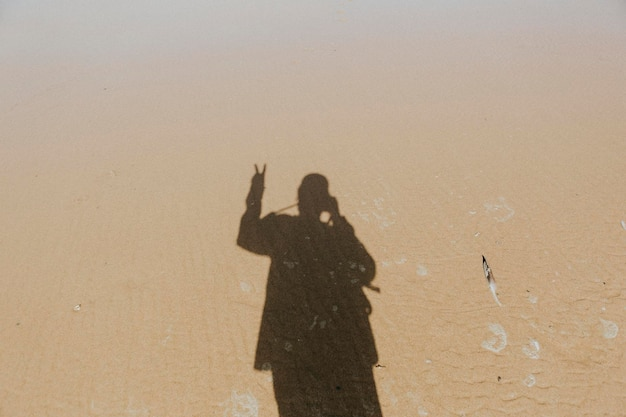 Calm waters over the sand with a shadow of a man