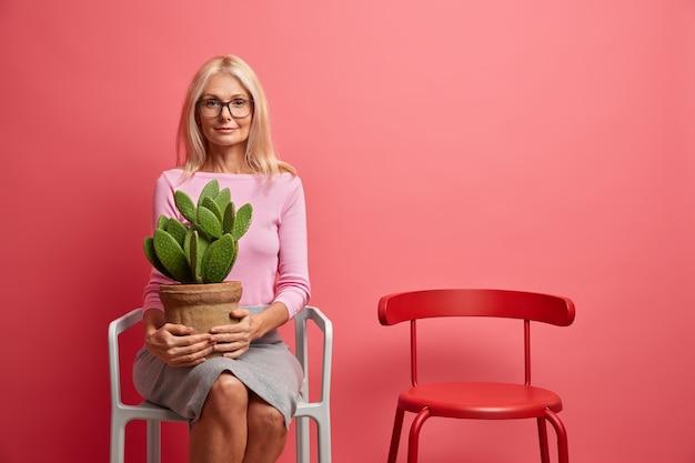 중년의 차분한 현명한 여자가 편안한 의자에 공상에 앉아 냄비에 선인장을 들고 고요한 표정이 안경 점퍼와 치마를 입습니다.