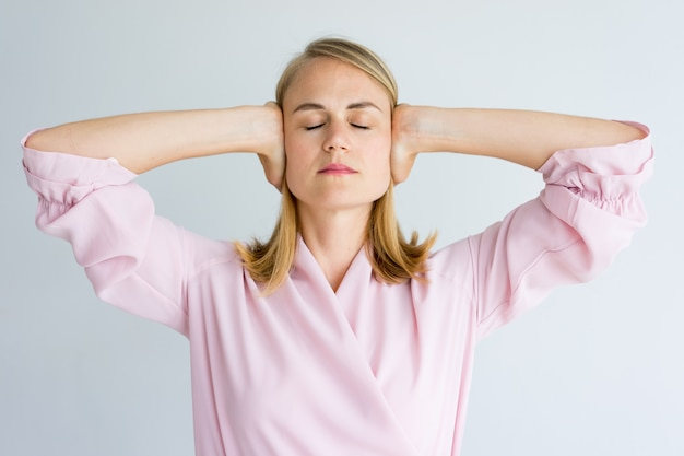 Calm woman covering ears while trying to concentrate.