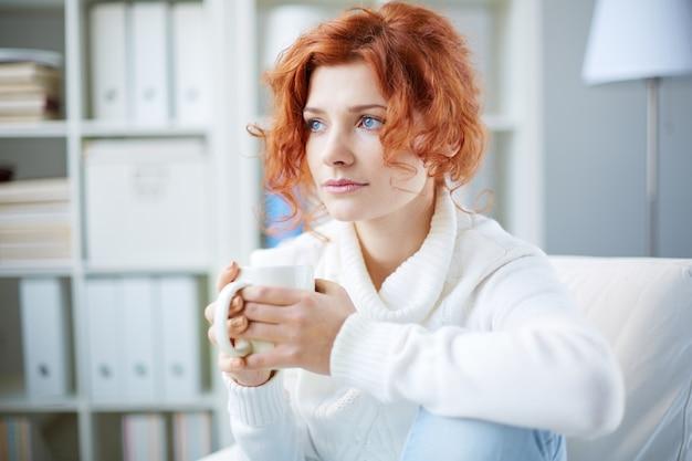 Calm woman having a hot drink