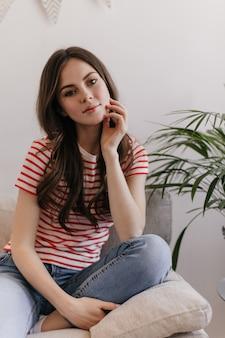 ジーンズとtシャツを着た落ち着いた女性がアパートで休んでいて、柔らかいソファに座っています