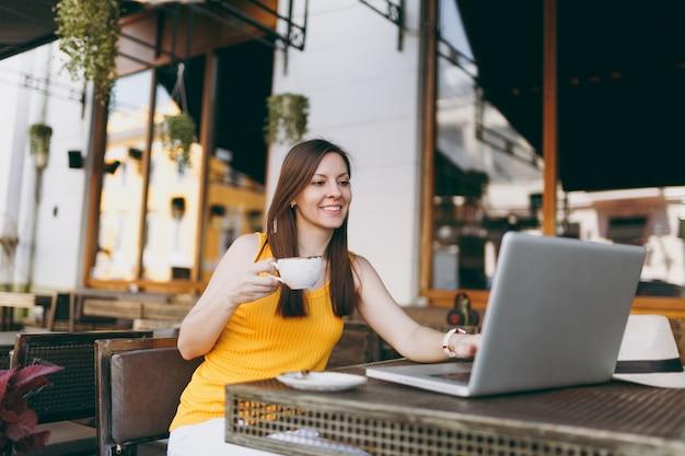 Спокойная женщина в уличном кафе-кафе на открытом воздухе сидит за столом, работает на современном портативном компьютере, пьет чашку чая, отдыхает в ресторане в свободное время