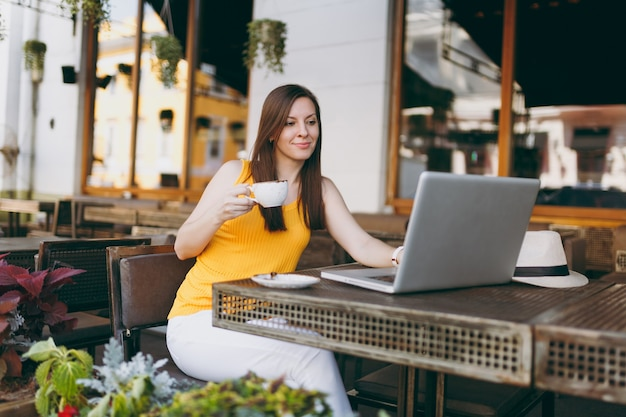 Calm woman in outdoors street coffee shop cafe sitting at table working on modern laptop pc computer, drink cup tea, relaxing in restaurant during free time