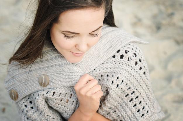 Спокойный женский портрет, сидящий на морском пляже, завернувшись в вязаный свитер