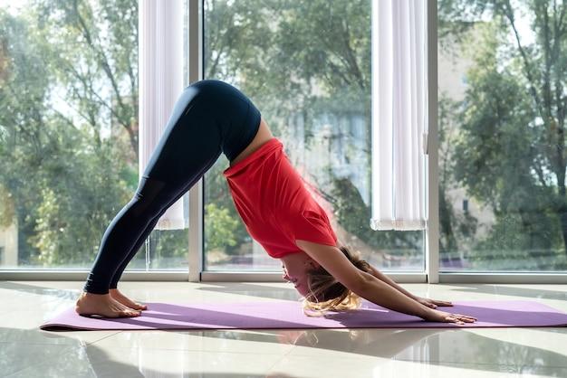 Спокойная женщина, практикующая йогу, делает упражнения на растяжку в гостиной дома возле больших окон