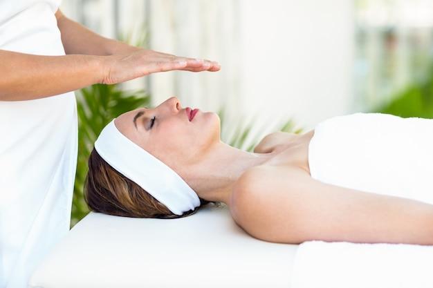 Спокойная женщина, получающая лечение рейки
