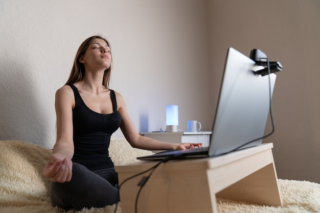 Calm woman relaxing meditating with laptop, no stress free relief at work concept, mindful peaceful young businesswoman or student practicing breathing yoga exercises at workplace
