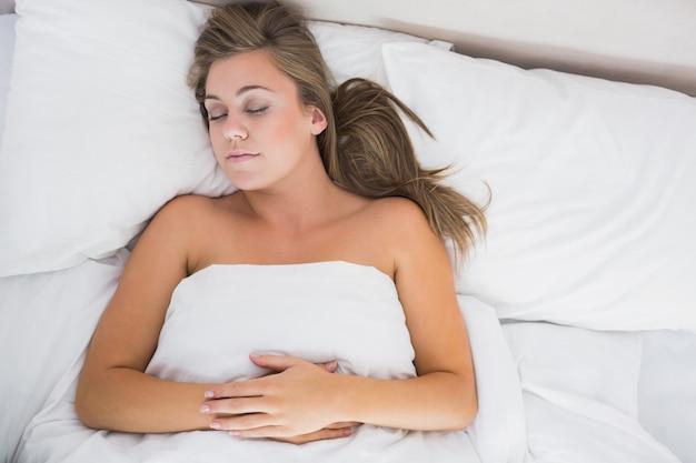 Calm woman sleeping in white bedroom