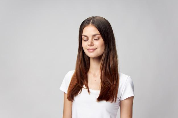 Спокойная женщина с закрытыми глазами, длинные волосы, белая футболка и серый