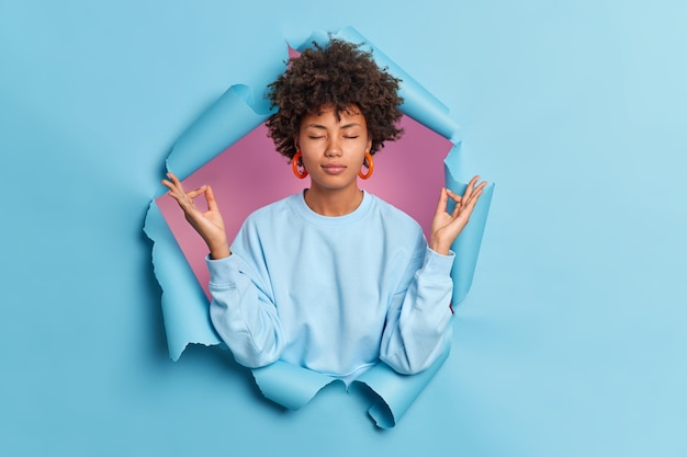 Calm woman with curly hair meditates with closed eyes breathes deeply relaxed with yoga spreads hands sideways in zen feels peace inside poses in ripped paper hole of blue wall