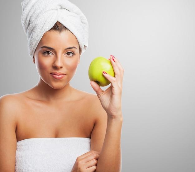 手で頭とリンゴにタオルで穏やかな女性