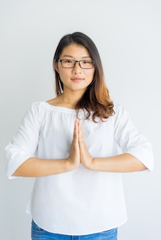 Calm yoga teacher making Namaste gesture for greeting.