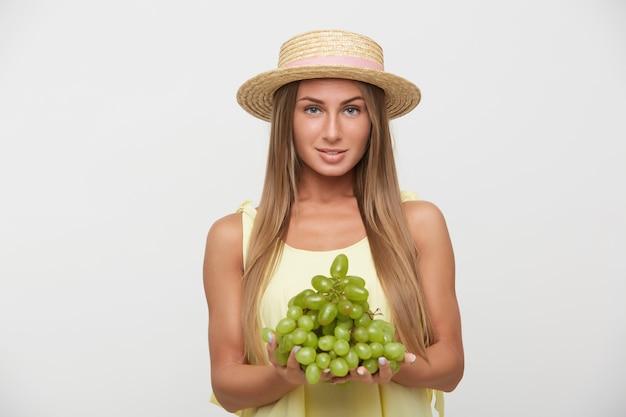 Спокойная молодая привлекательная блондинка с естественным макияжем, положительно смотрящая в камеру с легкой улыбкой, держа огромную гроздь зеленого винограда, позируя на белом фоне