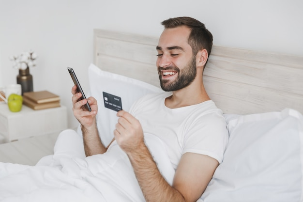 Calm young bearded man lying in bed with white sheet pillow blanket in bedroom at home