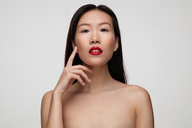 Calma giovane bella donna dai capelli scuri con labbra rosse e tenendo l'indice sollevato sulla guancia, isolato sopra il muro bianco