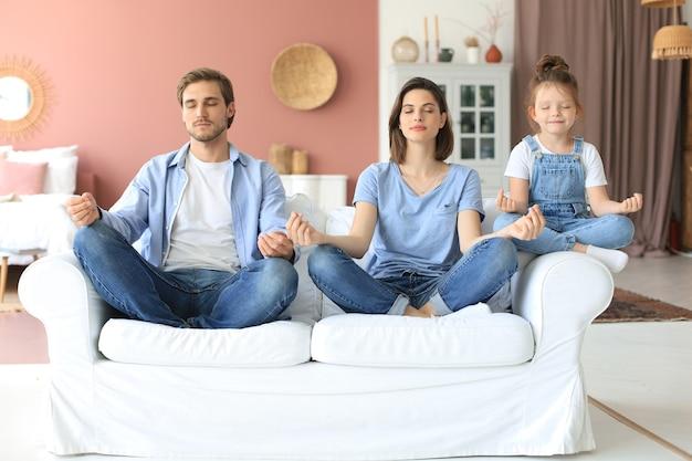 Спокойная молодая семья с маленькой дочкой сидят на диване, вместе занимаются йогой, счастливые родители с маленькой дошкольницей отдыхают на диване, медитируют, снимают негативные эмоции на выходных дома