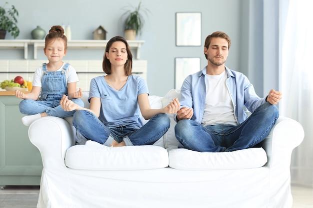 어린 딸이 있는 차분한 젊은 가족은 함께 소파에 앉아 요가 연습을 하고, 어린 미취학 아동을 둔 행복한 부모는 소파에 앉아 명상을 하며 주말에 집에서 부정적인 감정을 해소합니다